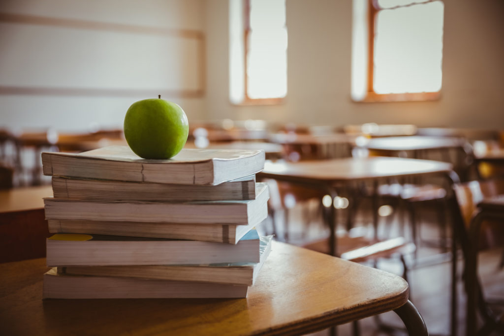 apple on stack of books ondesk in classroom